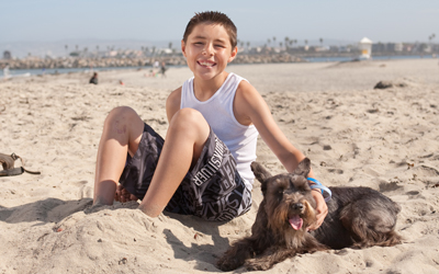 Victor, who suffered a severe brain injury and several broken bones in a bicycling accident, enjoys time on the beach with his buddy, Tucker.