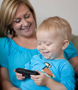 Luke, who received state-of-the-art care in Rady Children's Bernardy Center for Medically Fragile Children and through the Rady Children's Solid Organ Transplant Program, reacts to pictures of his brothers on a smartphone, while his mom Leah enjoys the moment.